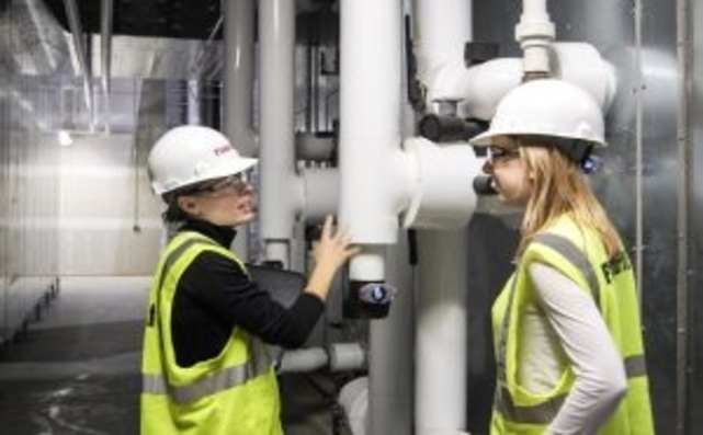 Two Females In Construction Gear Conversing