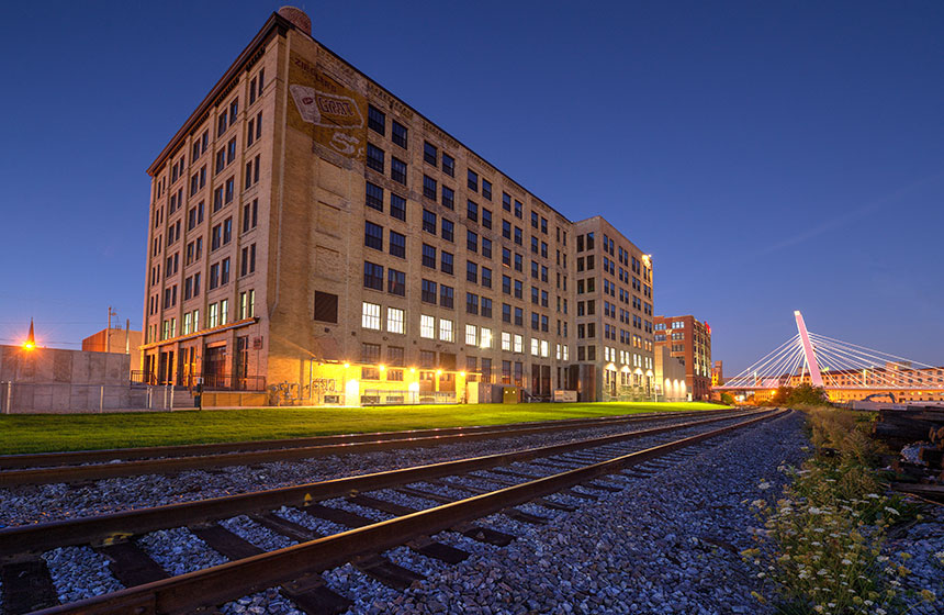 Outside of building at dusk, railroad tracks in the forefront