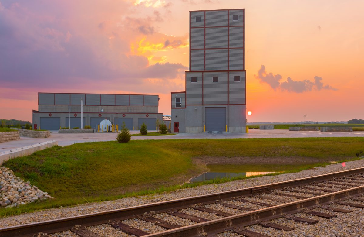 Outside of building at sunset, railroad tracks in the forefront
