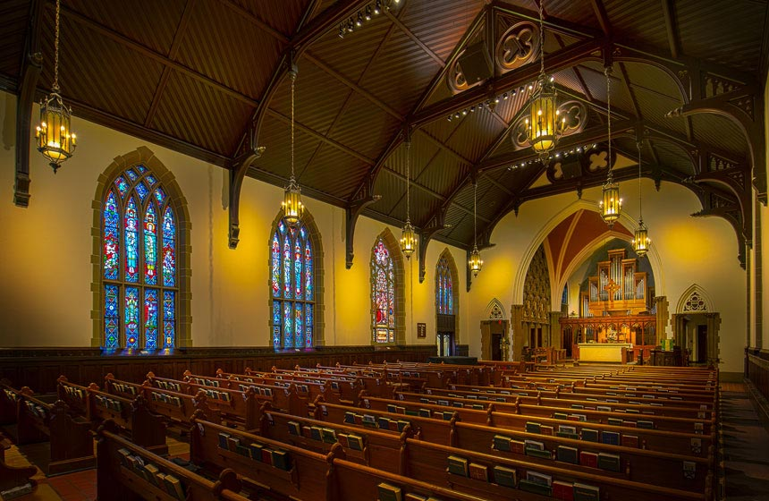 Inside of church; stain glass windows and pews