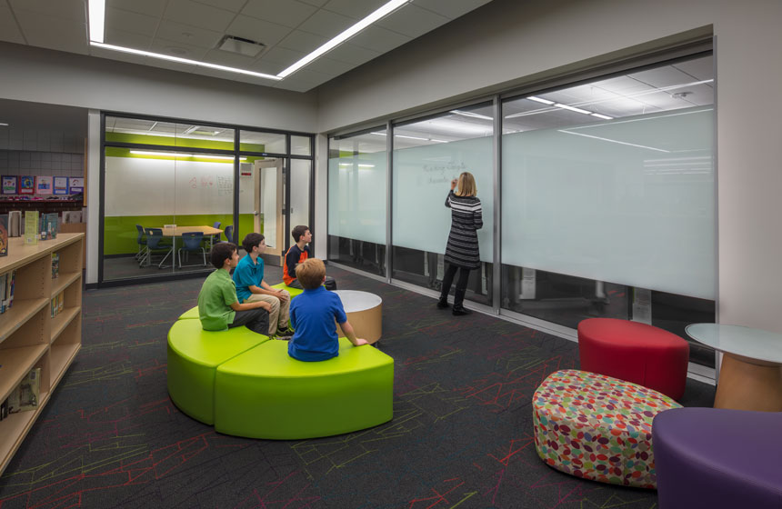 library with teacher writing on glass dry erase board with students on green seats
