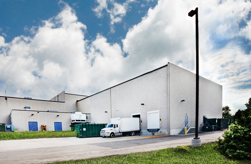 White warehouse with white truck outside of it